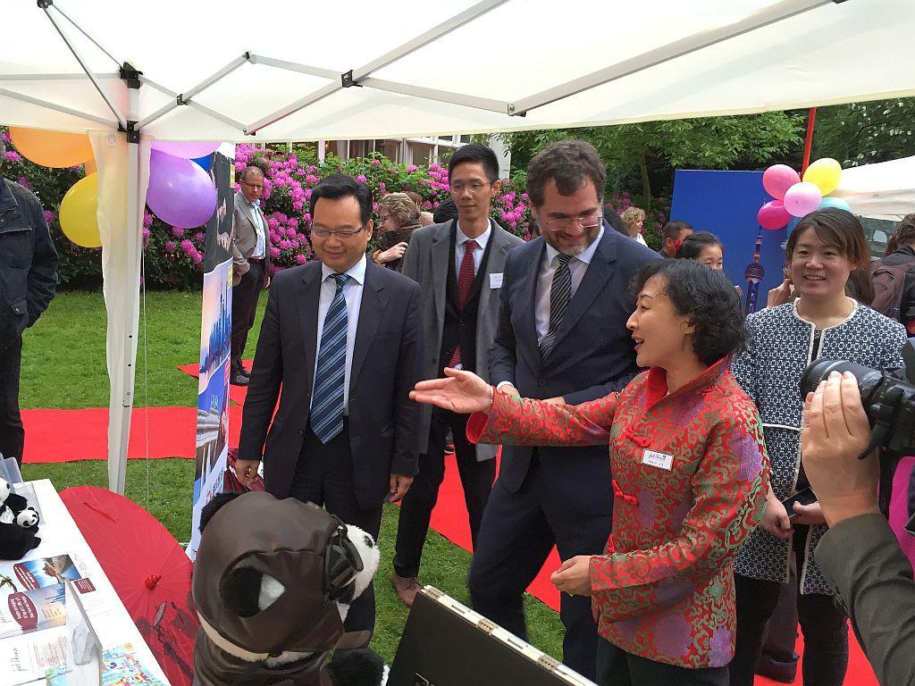 Frau Jin zeigt Herrn Generalkonsul Sun und Herrn Staatsrat Schmidt den Stand